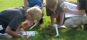 grade school students working outside on the grass, collaborating on 3d printed designs