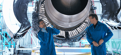 2 men working in the Aerospace industry, standing under a plane and making repairs together