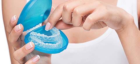 a woman holding 3d printed dental molds