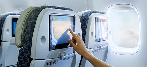 Woman reaching out to a touchscreen in aircraft interior