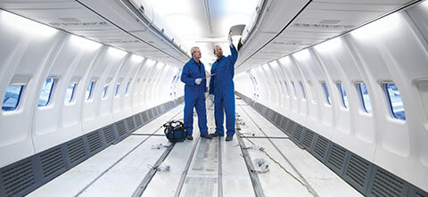 two men inside of an airplane with parts made from FDM Ultem 9085 Certified material