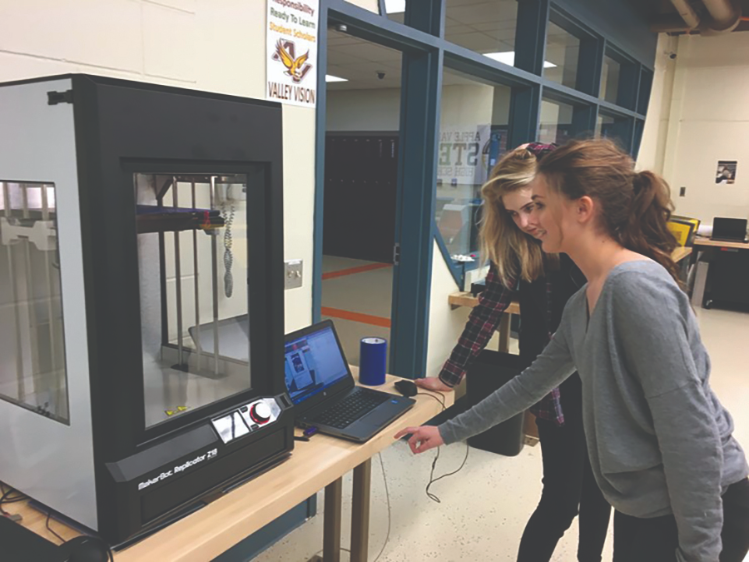 Two Apple Valley High School students watch the part they designed print.