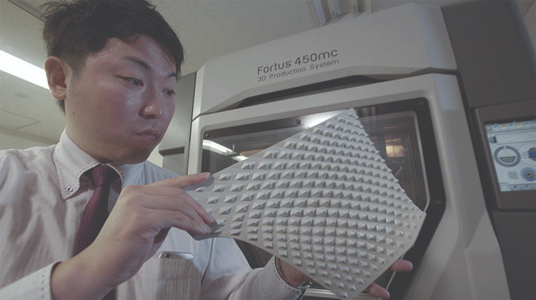 A man inspecting a 3d part with texture.