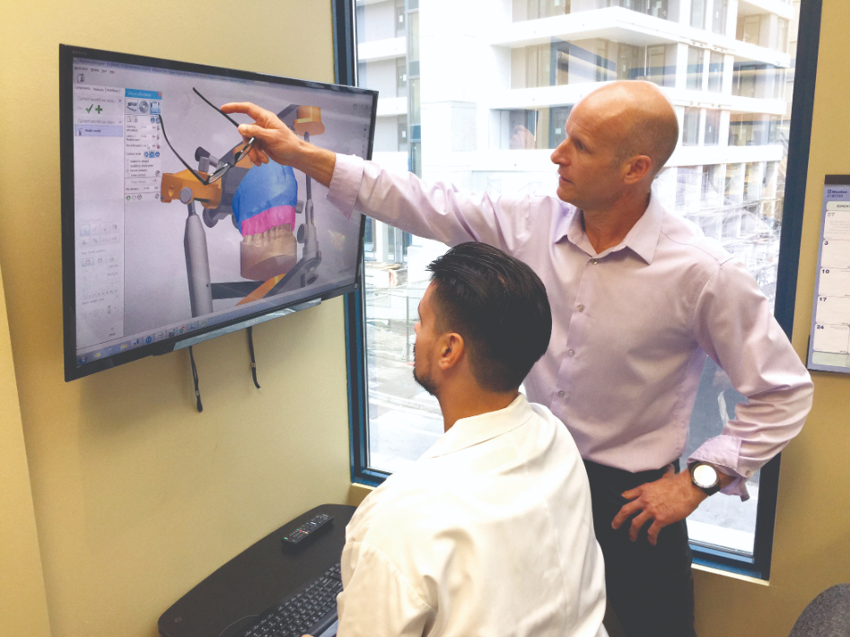 Two humans look over a splint on a computer screen.