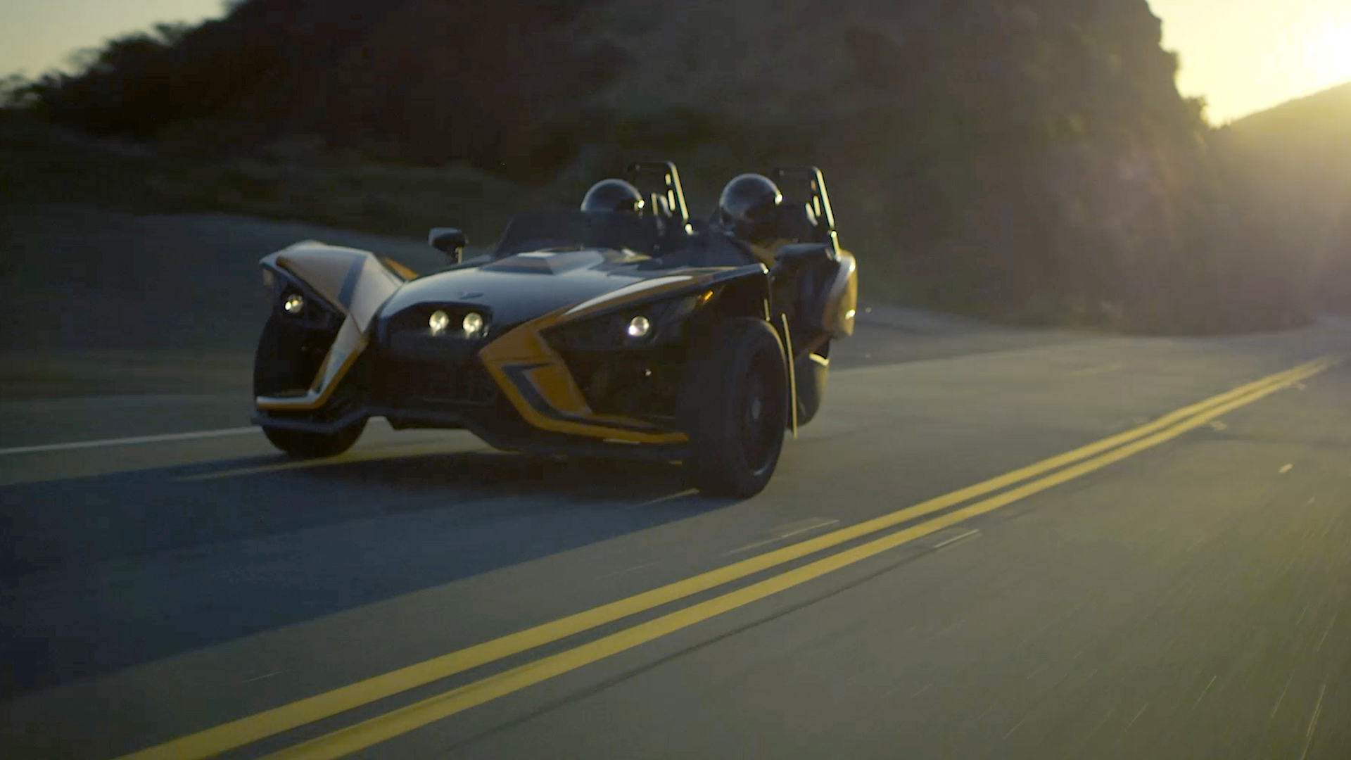 Two seat roadster driving down curvy road at dusk