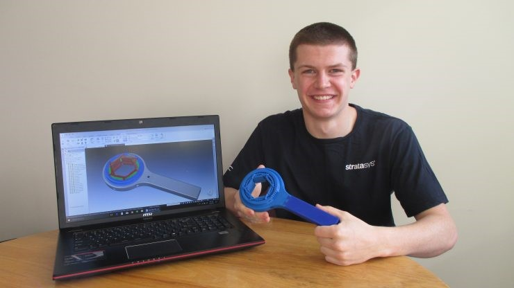 Student holding his 3D printed item next to his 3D printed design.