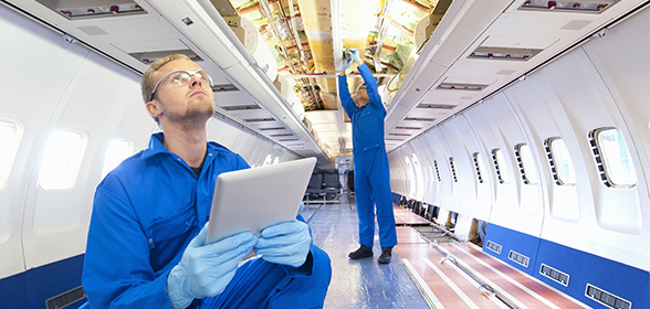 Two workers fixing interior of airplane