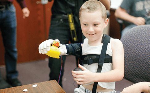 Six-year-old Alex Pring tries out his new 3D printed arm, created in part by a Dimension 3D Printer.