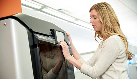 Woman using touch pad interface on the Stratasys F370 3D Printer