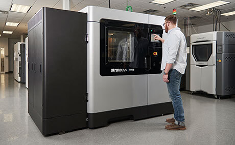 a man making a 3D print using a F900 Stratasys printer