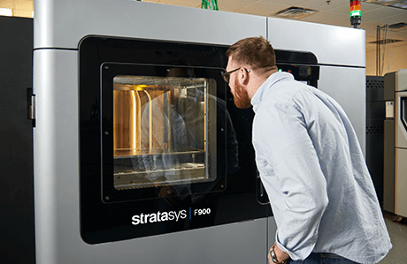 a man waiting for his 3D printed part next to a Stratasys F900 3D printer