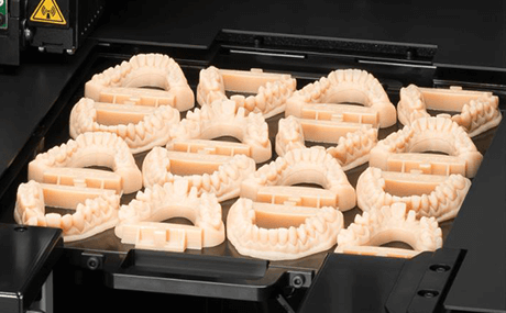 A close up of a 3D printer, where dental molds have just been printed