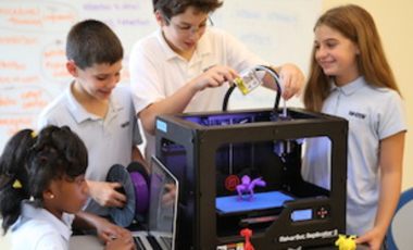 grade school students working on a 3D printer