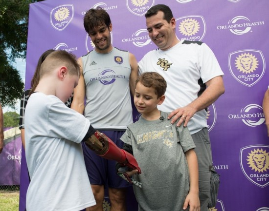 Paulo Costa Boa Nova and Alex Pring compare their Limbitless 3D printed arms as Kaká, the captain of the Orlando City Lions, and Paulo's father, Claudio, look on. Photo courtesy Orlando City Soccer Club.
