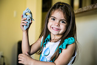 A happy and healthy five-year-old Mia holds a 3D printed replica of her heart 3D printed by Stratasys, which accurately shows the heart malformation that once caused debilitating symptoms.